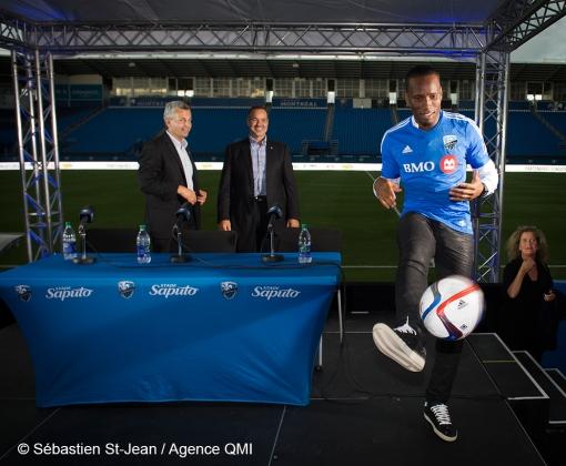 Didier Drogba (11), nouveau joueur de soccer de l'Impact de Montréal, lors d'une conférence de presse, au Stade Saputo, à Montréal, Québec, Canada, le jeudi 30 juillet 2015. Sur cette photo: Frank Klopas (Entraîneur-chef & Directeur du personnel des joueurs), Joey Saputo (Président de l'Impact de Montréal & Stade Saputo) et Didier Drogba, qui envoi un ballon dans la foule  SÉBASTIEN ST-JEAN/AGENCE QMI